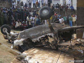 People gather around the wreckage of a plane that struck a building in the Kenyan capital of Nairobi on Saturday.