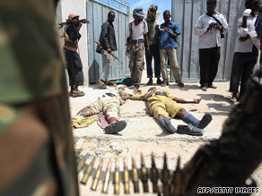 Al Shabaab fighters display two bodies of Somali police officers during a battle August 12 in Mogadishu.