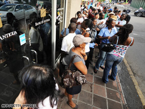 Customers queue outside the Stanford Group-owned Bank of Antigua in St. John's.