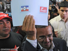 FMLN's Mauricio Funes shows his ballot before voting Sunday in Antiguo Cuscatlan, El Salvador.