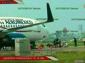 TV news footage shows suspects being seated in front of the hijacked plane on the tarmac at Mexico City's airport.