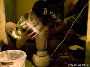 A gang member sniffs in a cloud of cocaine dust as he cuts the drug with other substances