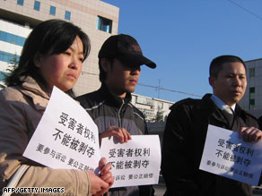"Victims' relatives outside a court hold banners that read ""cannot deprive the victims' rights."""