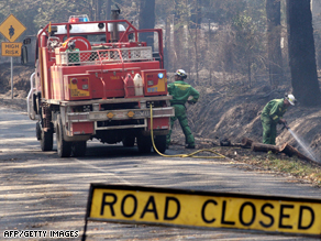 A fire crew douses hotspots on the edge of Healesville, north of Melbourne.