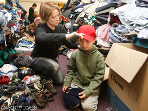 A woman dresses a  boy in donated clothes in Whittlesea, north of Melbourne.