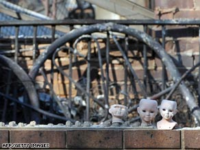 Porcelain dolls sit in front of a burnt house in the township of Phesant Creek, 100km north of Melbourne.