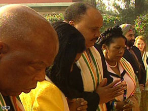 Martin Luther King III, center, reflects at the site of Mahatma Gandhi's memorial.