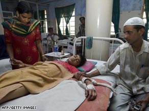Hepatitis-B patient Mahir Husain, center, is comforted at a hospital in Ahmedabad.