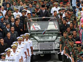 Malaysia's former PM Abdullah Badawi waves from a vehicle in Kuala Lumpur on Friday.