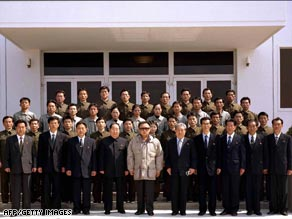 Picture released by North Korean state news agency shows Kim Jong Il, center, with staff from the rocket team.