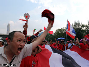 A supporter of former premier Thaksin Shinawatra wearing his mask at a protest in Bangkok.
