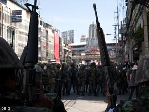 A wall of heavily-armed Thai troops closes in on protesters in central Bangkok.