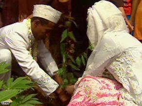 Cucu and his bride, Yati Supriyatna, plant two saplings during their wedding ceremony.