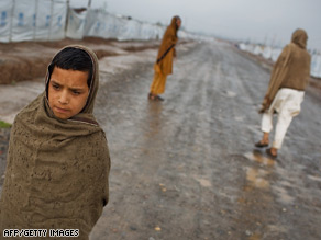 A young Pakistani boy walks through a camp in Peshawar, Pakistan after fleeing fighting between the Taliban and the Pakistan Army.