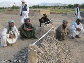 Villagers sit near the graves of victims of airstrikes in Garni, in western Farah province in Afghanistan.