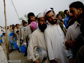Displaced civilians line up for a meal at Chota Lahore camp in Swabi district.