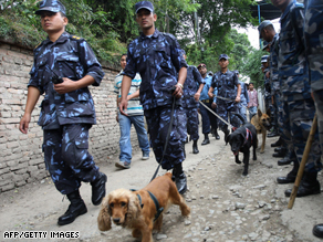 Police with sniffer dogs investigate the scene of a blast at a church in Kathmandu.