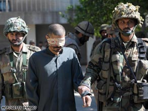 Pakistani solders escort a suspected Taliban militant inside an army base in Mingora.
