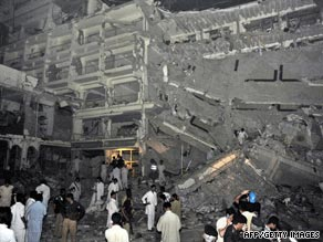 Pakistani police gather at the five-star hotel destroyed by a car bomb.