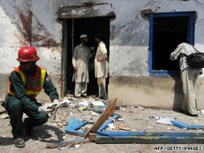 A Pakistani rescue worker works outside a damaged room of Jamia Naimia religious school.