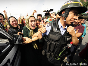 Ethnic Uyghur women grab the arm of a policeman as they protest in Urumqi on July 7.