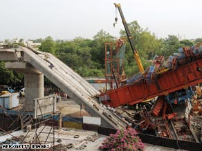 A crane clears away wreckage from a collapsed carriageway on Sunday in New Delhi, India.