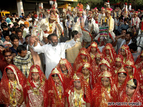 Young Indian men (rear) and women (front) are paraded before a mass wedding in 2006 in the village of Funda, 30kms from Bhopal.