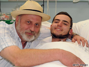 Jamie Neale recovers in a hospital bed in Katoomba, Australia, with his father Richard Cass after his ordeal.