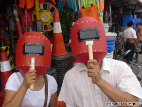 A couple try out welding screens bought from a hardware store to view the eclipse in Beijing on Tuesday.