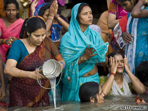 Hindu women pray as they bathe in the River Ganges after the total solar eclipse in India.