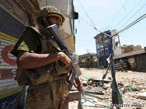 A Pakistani soldier patrols a ruined street in Mingora.
