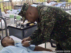 A wounded Philippine Marine receives a medal from Major Gen. Benjamin Dolorfino in Zamboanga Thursday.