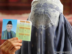 An Afghan woman in a burqa veil holds up a photograph of President Hamid Karzai.