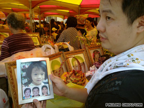 Tsai Sung Yu holds photos of his mother, brother, sister-in-law and niece who were all killed in the mudslides.