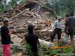Residents look at a collapsed house in West Java after a major earthquake rocked Indonesia on Wednesday.