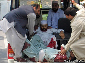 Hamid Saeed Kazmi (center) and his driver are helped into an ambulance at the site of the shooting.