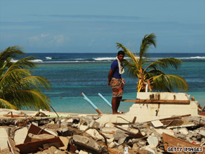 A man stands on the remains of what was once a tourist resort in Samoa's capital of Apia.