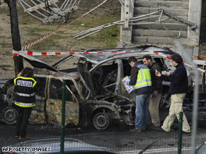 Policemen inspect the area after a van loaded with a bomb exploded in northeast Madrid.