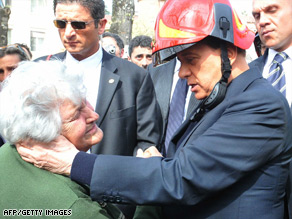 An elderly local resident bursts into tears during a visit by Silvio Berlusconi, wearing a fireman's helmet.