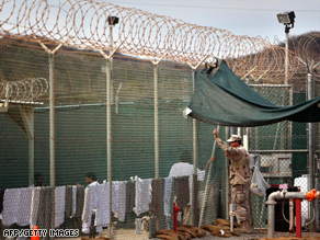 A guard leans on a fence and talks to a detainee at the Guantanamo Bay facility earlier this year.