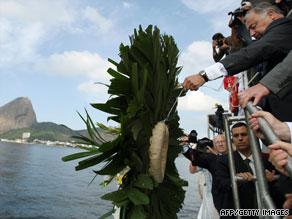 French Senator Gerard Larcher throws a tribute wreath into waters in Rio de Janeiro, Brazil, on Thursday.