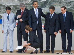 G-8 leaders wait for an aide to remove toe markers as they pose for a family photo in L'Aquila, Italy, on July 8.