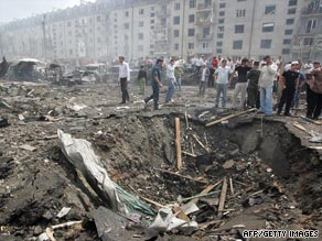 People stand near a crater caused by the blast in Narzon.