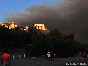 A wall of smoke forms a backdrop against the Acropolis of Athens as a blaze rages out of control.