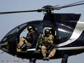 Heavily armed Blackwater guards scan downtown Baghdad, Iraq, from a helicopter in 2003.