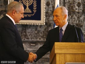 Netanyahu (left) shakes hands with Shimon Peres, who has asked him to form the next government.
