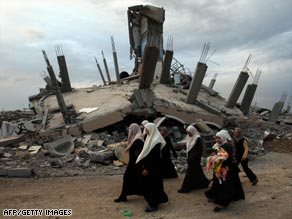 Palestinian women walk past a building destroyed during Israel's campaign in Gaza.