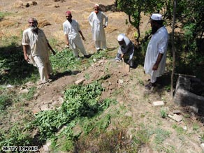 Pakistan residents cover a grave after burying a suspected Taliban militant, who was killed during fighting.