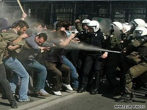 Demonstrators are sprayed with a water hose Saturday by Iranian security forces.