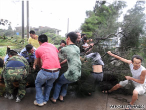 Residents gather to remove a fallen tree blocking a road in Changle, China, in Fujian province on Saturday.